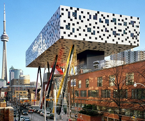 A photograph of the Sharp Centre for Design at OCAD University. The striking building features a two-storey table-top section standing over the original OCAD building on long multi-coloured stilts.