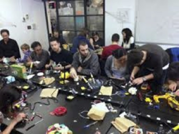 people sitting around a large black workshop table, hacking toys